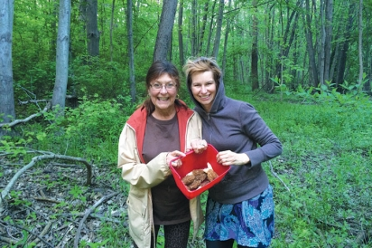 Two women pose in the woods of Goldberry Woods Bed and Breakfast