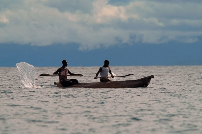 Two people use a canoe to catch catfish in Lake Malawi