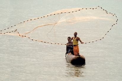 Two people on a boat cast a net for fish in Lake Malawi