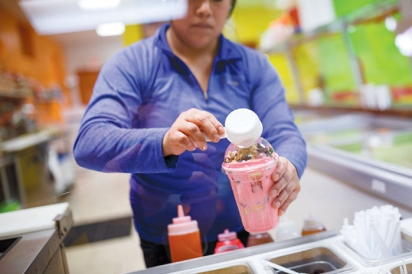 A woman pours dry toppings onto shaved ice