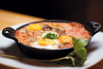 Eggs poached in red sauce made with spices including coriander