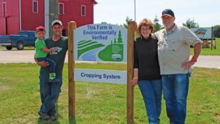 The Stover family stands in front of a sign signifying their farm, Berrien Springs, participates in the MAEAP program.